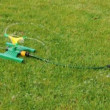 Stock Video: Lawn sprinkler splashing water over green grass.