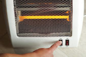 Electric heater and hand which includes switch — Stock Photo