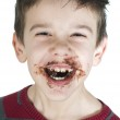 Smiling little boy eating chocolate — Stock Photo #16946639