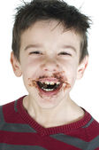 Smiling little boy eating chocolate — Stock Photo