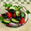 Salad in a glass bowl on a wooden base — Stock Photo