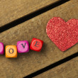 Word love on multicolored wooden cubes on wooden background — Stock Photo