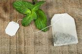 Tea bag and fresh mint — Stock Photo