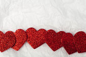 Shiny red hearts on white paper — Stock Photo