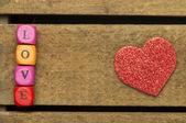 Slovo láska na barevné dřevěné kostky na dřevěné pozadí — Stock fotografie