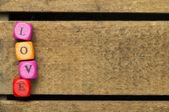 Slovo láska na barevné dřevěné kostky na dřevo — Stock fotografie