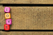 Word love on multicolored wooden cubes on wood — Stok fotoğraf