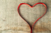 Red ribbon heart on wooden background — Stock Photo