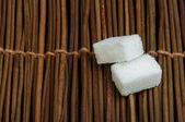 Sugar lumps on wooden base — Stock Photo
