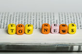 Word top news.Wooden cubes on magazine — Stock Photo