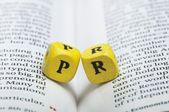 Word PR.Wooden cubes on magazine — Stock Photo