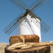 Different breads and windmill in the background — Stock Photo