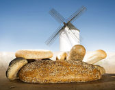 Different breads and windmill in the background — Foto Stock