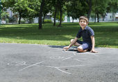 Child drawing family on asphalt — Stock Photo