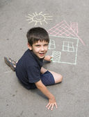 Child drawing sun and house on asphal — Stock Photo