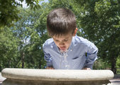 Child drinking water from a fountain — Stock Photo