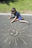 Child drawing on asphalt — Stock Photo