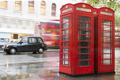 Red Phone cabines in London and vintage taxi.Rainy day. — Stock fotografie