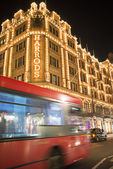 Harrods department store. Red bus passes in front of the buildin — Stock Photo