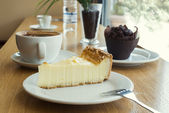 Cheesecake, muffin, coffee and mineral water — Stock Photo