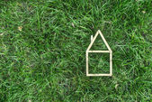Model house made on green grass — Stock Photo