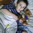 Sick child in bed with teddy bear — Foto Stock #40062891