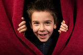 Child appearing beneath the curtain — Stock Photo