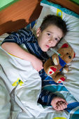 Sick child in bed with teddy bear — Stock Photo