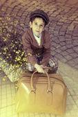Criança em uma estrada com bolsa vintage — Fotografia Stock