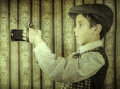 Child taking pictures with vintage camera — Stockfoto