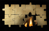 Burning wooden puzzle on dark background. — Stock Photo