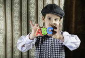 Child in vintage clothes hold letters a b c — ストック写真