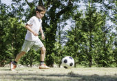 Child playing football in a stadium — Stock Photo