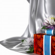 Holiday background flowers with cloth and gift box — Stock Photo
