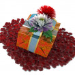 Holiday flowers with gift box and rose petals as form of heart — Stock Photo