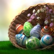 Decorated Easter eggs on the grass in basket — Stock Photo #22849852