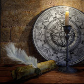 Ancient still life with candle and scroll concept background — Stock Photo