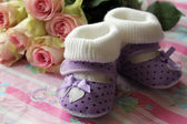 Greetings from newborn birth of his daughter - shoes and flowers — Stock Photo