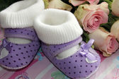 Congratulation with a newborn - baby shoes and flowers — Stock Photo