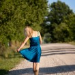 Woman walking away on dirt road — Stock Photo #22123733