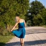 Woman walking away on dirt road — Stock Photo