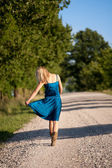 Woman walking away on dirt road — Stock Photo