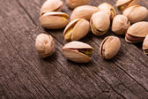 Pistachios on wooden surface — Stock Photo
