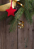 Fir branches and star on old wooden background — Stock Photo