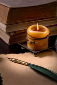 Quill pen, candle and  books — Stock Photo