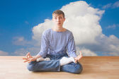 Teenager making funny face while sitting in lotus pose — Stock Photo