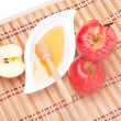 Apple half and saucer of honey — Stock Photo