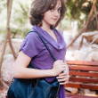 Teenage girl in lilac dress walking through park — Stock Photo
