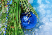 Blue necklace and a ball on Christmas tree — Stock Photo