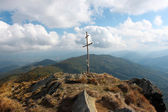 Wooden cross on top of a rocky hill — Stock Photo